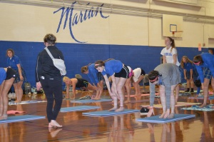 President Ms. Mary Higgins instructs the crowd at the first Yoga Club meeting of the year. Photo by Clara Wertzberger.