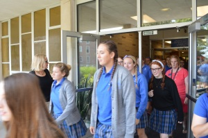 Principal Susie Sullivan holds the door as students file out on Aug. 21 for the first test of the fire drill evacuation policy.  Photo by Molly Miller.