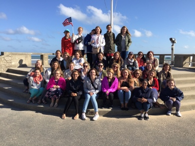 Marian Takes Frelgium. All the students in the France and Belgium trip pose for a photo at Normandy Beach. Photo courtesy of Mrs. Remmick.