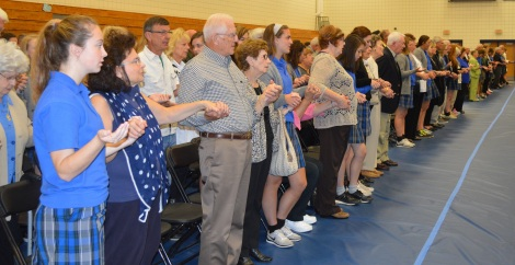 Glory and Praise: Grandparents join hands with their Marian granddaughters at Mass on the morning of Oct. 8. More than 700 grandparents joined the girls for the day's festivities. photo by emily mckenna